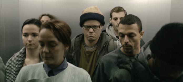 Robert Daly sério em um elevador lotado, a caminho do escritório