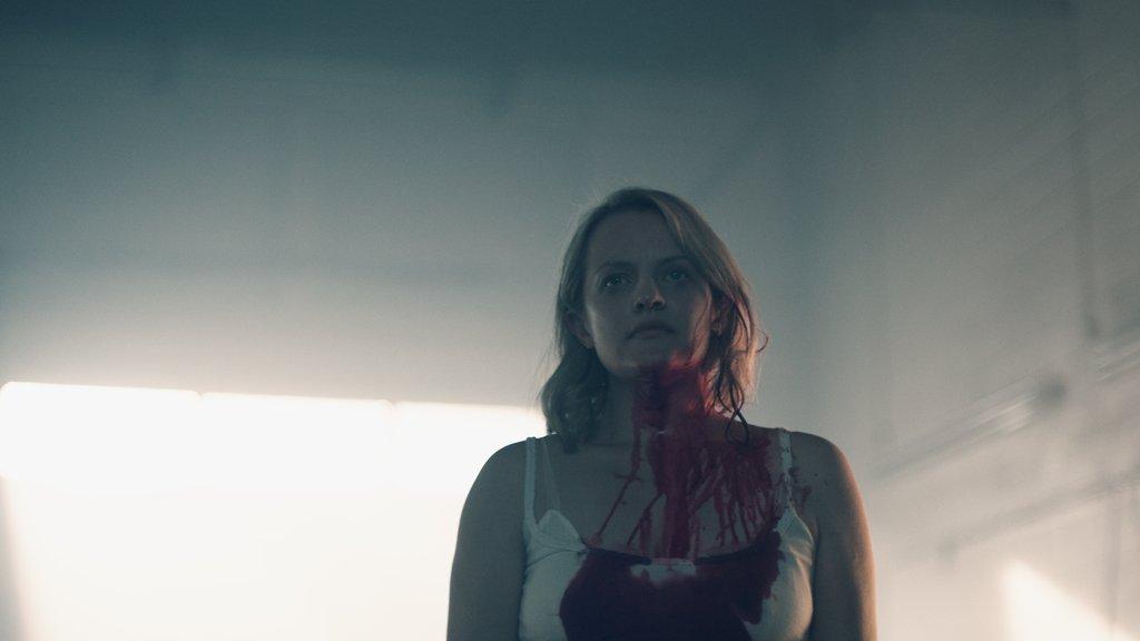 Foto da personagem Offred, interpretada por Elisabeth Moss, ensanguentada, mas com expressão resoluta.