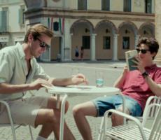 Cena do filme Me Chame pelo seu Nome que mostra Elio e Oliver sentados em uma mesa de café em uma praça.